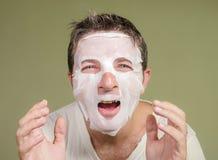 Naturlig st?ende av den unga lyckliga och roliga mannen som applicerar den ansikts- maskeringen f?r sk?nhet som ser i skratta f?r royaltyfri fotografi