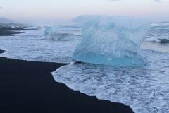 Naturlig svart sandstrand med is som överst bryter Arkivbilder
