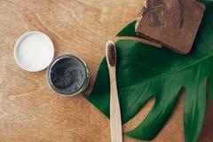 Naturlig tandkräm aktiverade kol- och bambutandborsten på träbakgrund med det gröna monsterabladet Plast- fri skönhet royaltyfria foton
