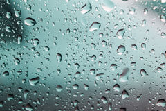 Naturlig vattendroppe på exponeringsglas, vatten tappar Arkivfoto