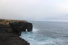 Naturlig vulkanisk havsbåge på en stenig kustlinje Royaltyfri Fotografi