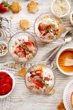 Naturlig yoghurt med nytt nytt jordgubbar, granola, honung, muttrar och frö i glass disk Läcker frukost eller efterrätt royaltyfri bild