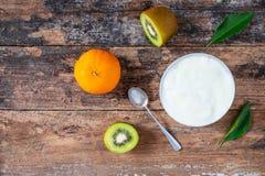 Naturlig yoghurt och frukt på trätabellen fotografering för bildbyråer