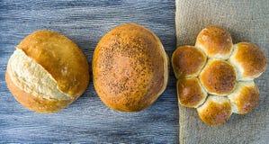 Naturliga brödbageribilder, kalkonbrödtyper, formade bröd, släntrar brödvariationer, olika typer av bröd på trägolv Fotografering för Bildbyråer