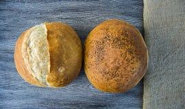Naturliga brödbageribilder, kalkonbrödtyper, formade bröd, släntrar brödvariationer, olika typer av bröd på trägolv Royaltyfri Fotografi
