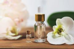 Naturliga flaskor för nödvändig olja för blomma med orkidéblomningen arkivbild