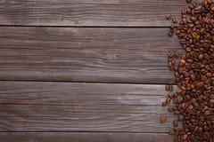 Naturliga kaffebönor på grå träbakgrund arkivbild