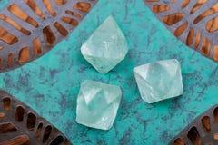 Naturliga Octahedronkristaller för grön Fluorite på den koppargröna plattan royaltyfri bild