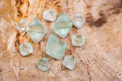 Naturliga Octahedronkristaller för grön Fluorite på den naturliga polerade tjock skiva för förstenat trä arkivbild