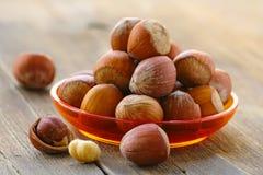 Naturliga organiska hasselnötter i en bunke Royaltyfri Bild