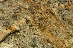Naturliga stenar och att vagga fragment på berglutningarna nära Blacket Sea som en original- och textural bakgrund Brunt gult, arkivfoton