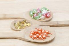 Naturliga vitaminer för goda hälsor i en träsked på en träbakgrund Royaltyfria Bilder