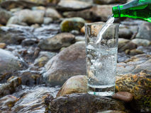 Naturligt dricksvatten hälls in i exponeringsglas Royaltyfri Fotografi
