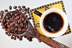 Naturligt kaffe i en kopp och kaffebönor i en sked, en stärkande drink Kaffe är trevligt att dricka i morgonen på frukosten royaltyfria bilder