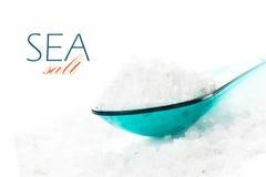 Naturligt salt av det döda havet i kulör sked på vit bakgrundscl royaltyfria bilder