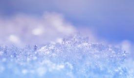 Naturligt skimrar många kristaller av snöflingor av olik former och textur på solen på en klar vinterdag mot en blå himmel arkivfoto