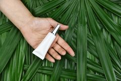 Naturligt skincareskönhetsproduktbegrepp, kosmetiska flaskbehållare i hand på grön växt- sidabakgrund royaltyfri fotografi
