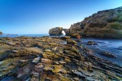 Naturligt vagga bågen, klippan och stranden arkivfoto