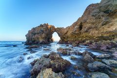 Naturligt vagga bågen, klippan och stranden arkivfoton