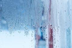 Naturligt vatten tappar på exponeringsglas, fönsterexponeringsglas med kondensation, stark hög fuktighet, stora droppar av vatten arkivfoton