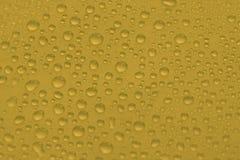 Naturligt vatten tappar på gul guld- bakgrundstextur Arkivbilder
