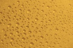 Naturligt vatten tappar på gul guld- bakgrundstextur Arkivfoto