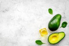 Naturprodukte für Hautpflege Avocadoöl in den Flaschen nahe schnitt Avocado auf grauem Draufsicht-Kopienraum des Hintergrundes lizenzfreie stockbilder