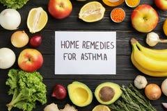 Naturprodukter och anmärkning med textHEMBOTER FÖR ASTMA på träbakgrund royaltyfria foton