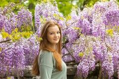 Naturschönheit: rotes Haarmädchen und Sommersprosseglühenhaut auf den purpurroten Blumen Lizenzfreies Stockbild