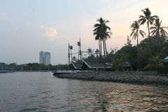 Naturschönheits-Kokosnussbaum-Uferabend-Sonnenuntergangzeit des ruhigen Sees Stockfotos