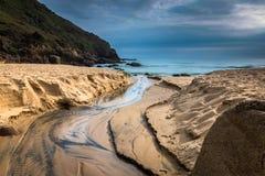 NaturSeascape med en ström över Sandy Beach in mot havet royaltyfri fotografi