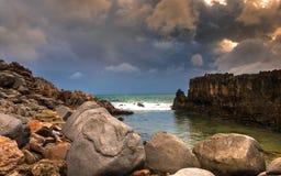 NaturSeascape med grovt vaggar, vågen, mörka moln och himmel under en storm på soluppgång royaltyfri bild