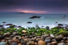 NaturSeascape med vaggar täckt av gröna mossor, suddiga vågor och mörk molnig himmel fotografering för bildbyråer