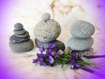Natursteine und Stiefmütterchenblumen auf altem Gewebe Stockfotografie