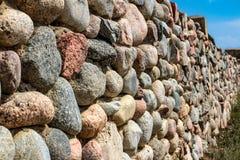 Natursteinwand des runden Steins, der Front und des hinteren Hintergrundes verwischt mit bokeh Effekt stockfotos