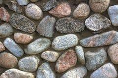 Natursteinwand des runden Steins, der Front und des hinteren Hintergrundes verwischt mit bokeh Effekt lizenzfreie stockbilder