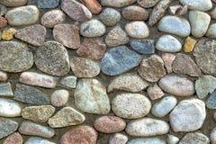 Natursteinwand des runden Steins, der Front und des hinteren Hintergrundes verwischt mit bokeh Effekt lizenzfreies stockbild