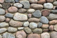 Natursteinwand des runden Steins, der Front und des hinteren Hintergrundes verwischt mit bokeh Effekt stockfoto