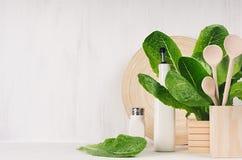 Natuurlijk beige houten keukengerei en groene installatie op lichte witte houten achtergrond, exemplaarruimte Stock Fotografie