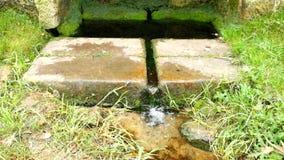 Natuurlijk drinkwater van bergstroom Steenachtige landelijke fontein in het bos met vers glashelder water stock videobeelden