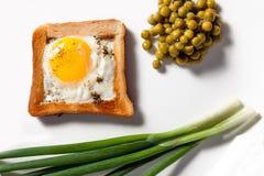 Natuurlijk gebraden ei met groene uien en ingeblikte erwten Royalty-vrije Stock Foto's