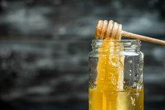 Natuurlijk, gezond ingrediënt - een kruik gouden honing op een donkere achtergrond royalty-vrije stock foto