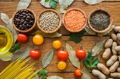 Natuurlijk gezond voedsel Vier kommen met kruiden, koffiebonen en linzen op een achtergrond op houten lijst Hoogste mening concep stock fotografie