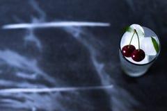 Natuurlijk ijs in een glas met kersen op een zwarte achtergrond Stock Afbeeldingen
