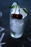 Natuurlijk ijs in een glas met kersen op een zwarte achtergrond Royalty-vrije Stock Foto