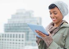 Natuurlijk jong model in de winterkleren die een tabletpc met behulp van royalty-vrije stock afbeeldingen