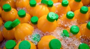 Natuurlijk jus d'orange in oranje vormflessen op verpletterd ijs ref royalty-vrije stock afbeelding