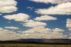 Natuurlijk landschap met blauwe hemel, pluizige wolken en de Ural-bergen Stock Afbeeldingen
