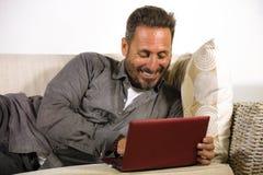 Natuurlijk levensstijlportret van jonge knappe en succesvolle zelf - tewerkgestelde mens die thuis gebruikend laptop computer ont stock afbeeldingen