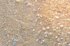 Natuurlijk rond gemaakte grint op zee kust, aard overzeese achtergrond Stock Afbeeldingen